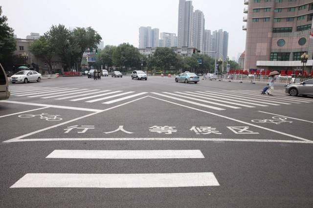 人行安全岛与岛上的行人过街交通信号灯相配合,通过对行人过街进行半