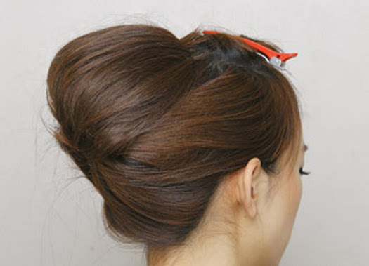 步骤五:将两边的头发分别包裹住脑后的发簪内扭转起来.图片