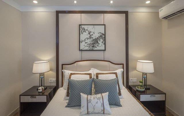 另一个卧室的床头背景墙与前面的类似,不过两侧却增加了中式的造型与图片