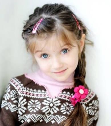 编织的双马尾小辫子,额前用蝴蝶结发夹装饰,整体发型将小女孩古灵精怪