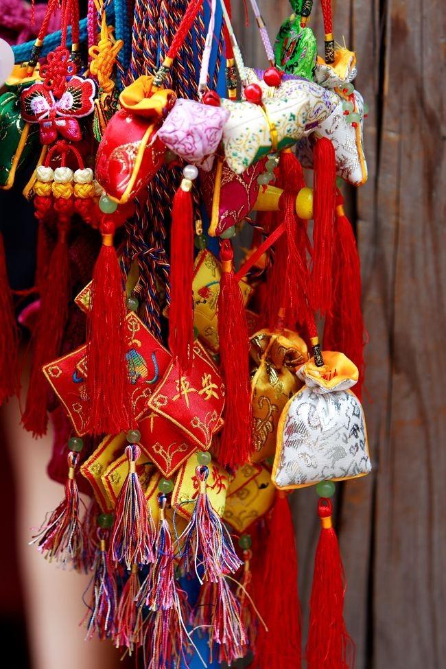 她找来多彩的布头 还有五色彩线 和邻居的大娘大嫂 缝制小巧的动物佩