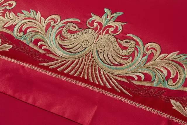 红色提花面料传递出新婚燕尔的情愫,整版绣花的金色凤鸟图案形似欧式