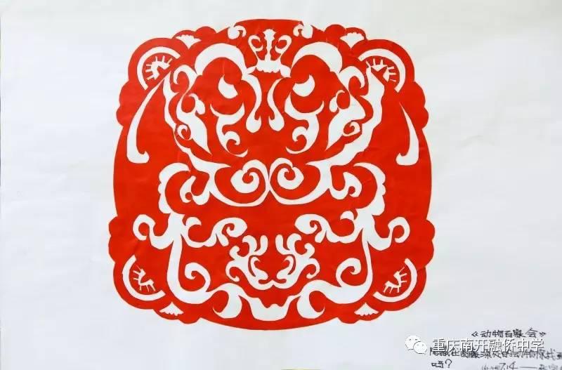 """剪纸的方式制作了一幅轴对称图形,并留言""""你能找到隐藏在图形中的动物"""