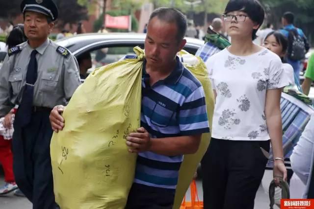 一名农村父亲用编织袋扛着孩子的行李.