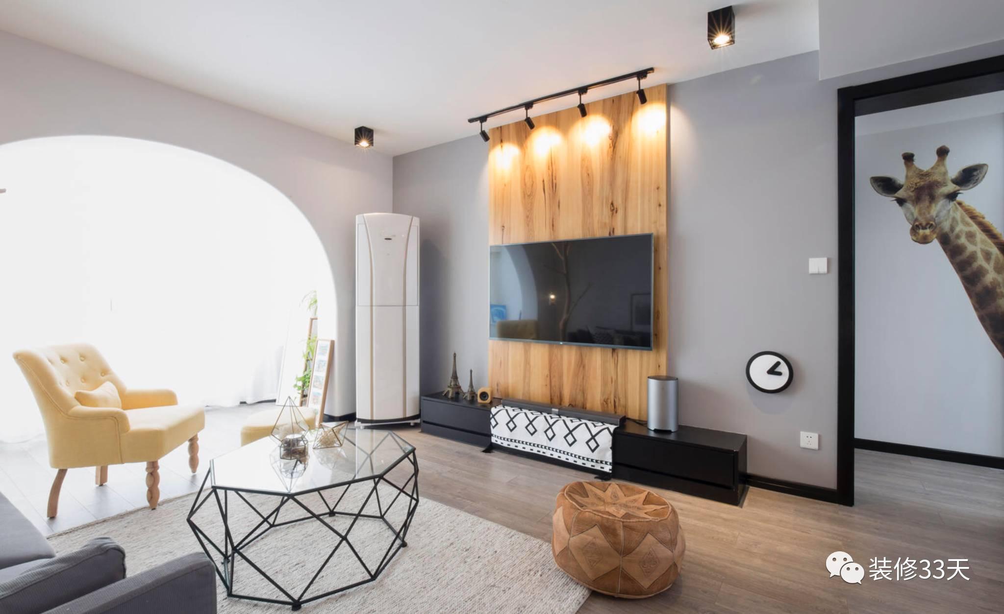 黑白灰的基调,布艺沙发柔软舒适,背景用一幅木饰边框画装饰,铁艺茶几