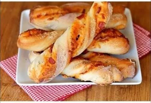 第一步:将发酵好的面团擀成长条状,铺上披萨酱和切成小片的火腿