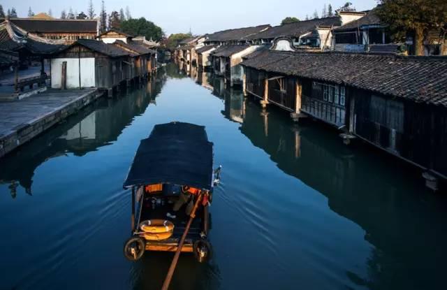 乌篷船是江南水乡的地域符号, 常常出没在密集水巷之间