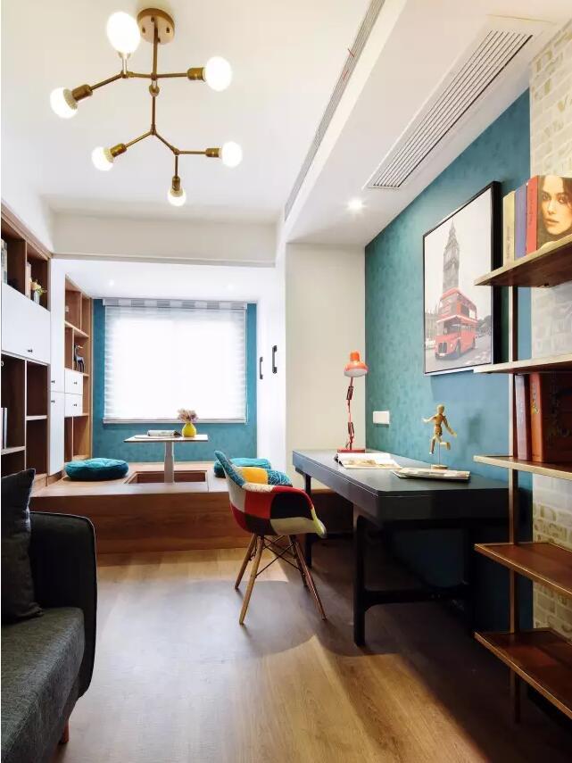 ▲ 书房木质地面,局部铺贴色彩壁纸,灰色沙发,层板书架,实木书桌