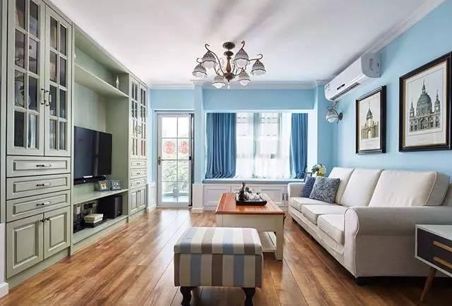 客厅的电视背景墙是一整墙的电视柜,特别能收纳物品,柜子是浅绿色的